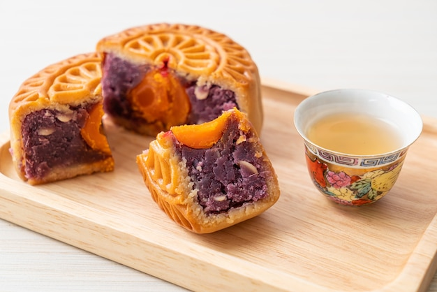 Chinese moon cake purple sweet potato flavour with tea on wood plate