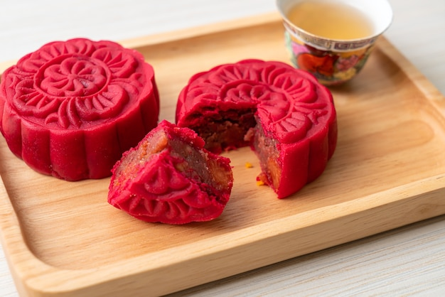 Chinese moon cake strawberry red bean flavour on wood plate