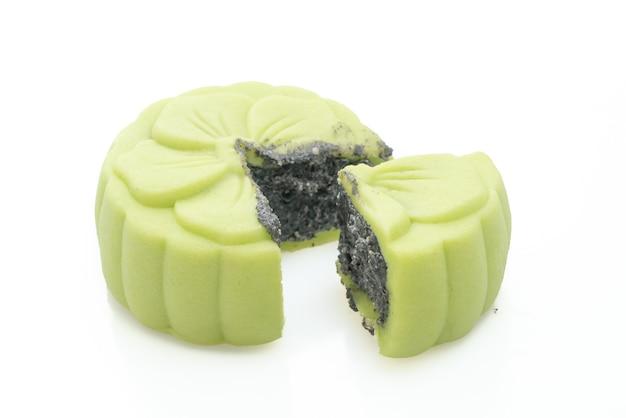 Китайский лунный пирог со вкусом зеленого чая с черным кунжутом на белой поверхности