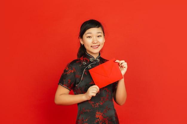 中国の旧正月2020。赤い背景で隔離のアジアの若い女の子の肖像画。伝統的な服を着た女性モデルは、幸せそうに見え、笑顔で赤い封筒を持っています。お祝い、休日、感情。
