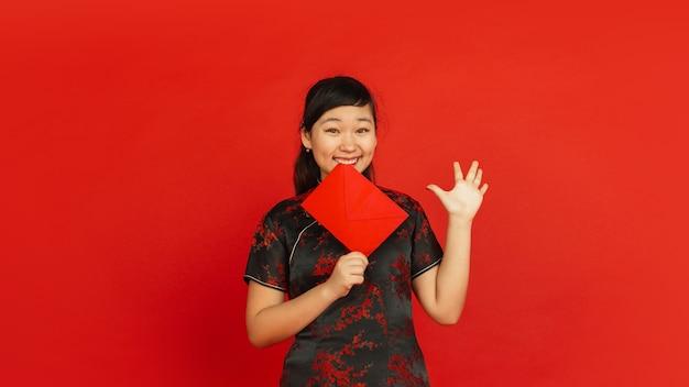 中国の旧正月2020。赤い背景で隔離のアジアの若い女の子の肖像画。伝統的な服を着た女性モデルは、幸せそうに見え、笑顔で赤い封筒を見せています。お祝い、休日、感情。