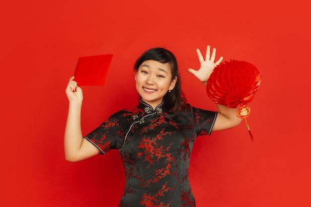 中国の旧正月2020。赤い背景で隔離のアジアの若い女の子の肖像画。伝統的な服を着た女性モデルは、装飾と赤い封筒に満足しているように見えます。お祝い、休日、感情。