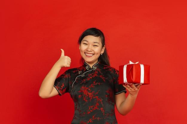 中国の旧正月2020。赤い背景で隔離のアジアの若い女の子の肖像画。伝統的な服を着た女性モデルは、ギフトボックスに満足しているように見えます。お祝い、休日、感情。素敵な笑顔を見せています。