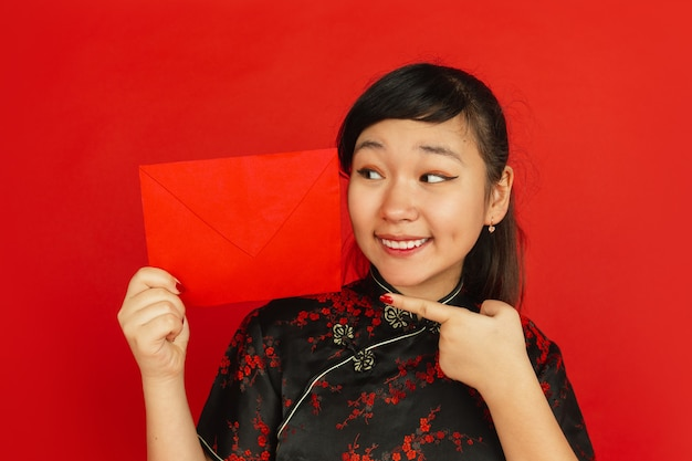 Chinese new year 2020. asian young girl's portrait isolated on red background. close up of female model in traditional clothes looks happy and showing red envelope. celebration, holiday, emotions.
