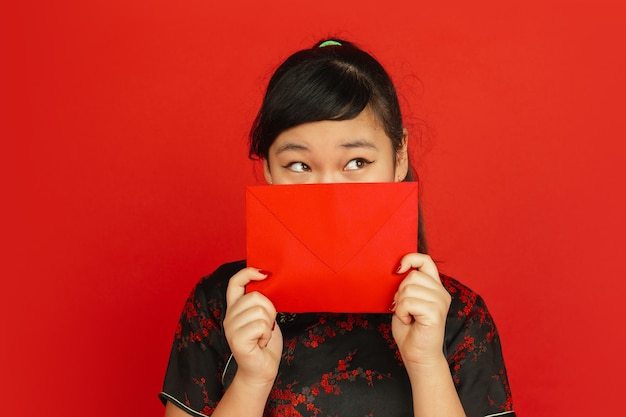 Chinese new year 2020. asian young girl's portrait isolated on red background. female model in traditional clothes looks dreamful and showing red envelope. celebration, holiday, emotions.