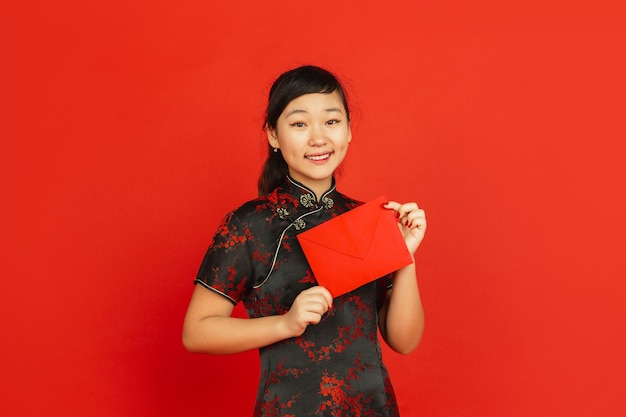 Chinese new year 2020. asian young girl's portrait isolated on red background. female model in traditional clothes looks happy, smiling and holding red envelope. celebration, holiday, emotions.