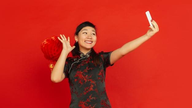 Chinese new year 2020. asian young girl's portrait isolated on red background. female model in traditional clothes looks happy and taking selfie with decoration. celebration, holiday, emotions. flyer.
