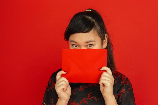 중국의 설날. 빨간색 배경에 고립 된 아시아 젊은 여자의 초상화. 전통적인 옷을 입은 여성 모델은 꿈꾸며 빨간 봉투를 보여줍니다. 축하, 휴일, 감정.