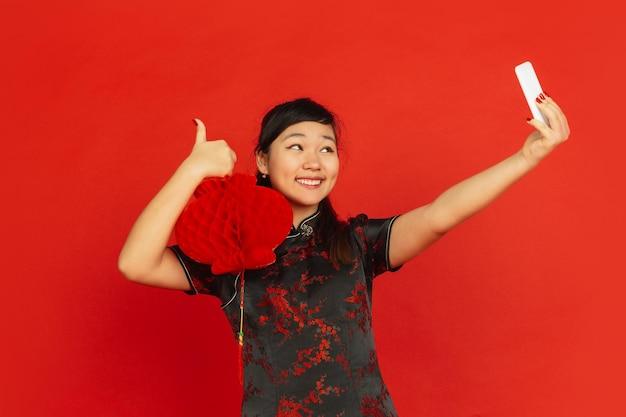 中国の旧正月。赤い背景で隔離のアジアの若い女の子の肖像画。伝統的な服を着た女性モデルは幸せそうに見え、装飾を施したセルフィーを撮ります。お祝い、休日、感情。