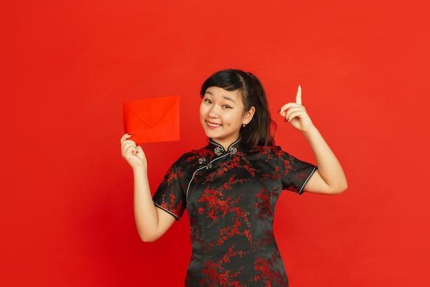 中国の旧正月。赤い背景で隔離のアジアの若い女の子の肖像画。伝統的な服を着た女性モデルは、幸せそうに見え、笑顔で赤い封筒を指しています。お祝い、休日、感情。