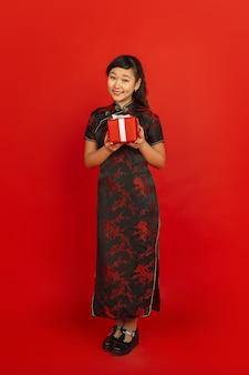 중국의 설날. 빨간색 배경에 고립 된 아시아 젊은 여자의 초상화. 전통적인 옷을 입은 여성 모델은 행복하고 웃고 선물 상자를 보여줍니다. 축하, 휴일, 감정.