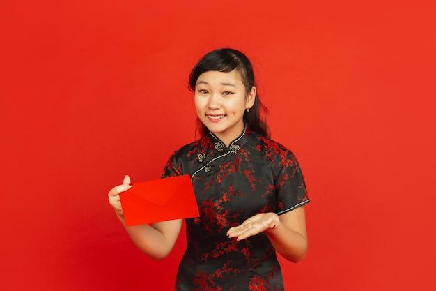 중국의 설날. 빨간색 배경에 고립 된 아시아 젊은 여자의 초상화. 전통적인 옷을 입은 여성 모델은 행복하고 웃고 빨간 봉투를 보여줍니다. 축하, 휴일, 감정.