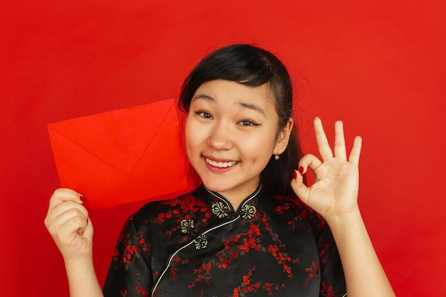 Chinese new year. asian young girl's portrait isolated on red background. close up of female model in traditional clothes looks happy and showing red envelope. celebration, holiday, emotions.