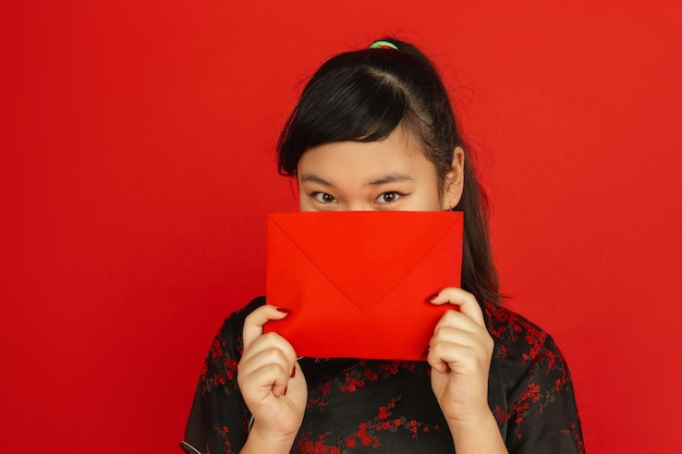 Chinese new year. asian young girl's portrait isolated on red background. female model in traditional clothes looks dreamful and showing red envelope. celebration, holiday, emotions.