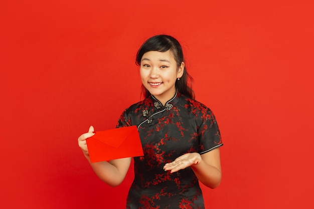 Chinese new year. asian young girl's portrait isolated on red background. female model in traditional clothes looks happy, smiling and showing red envelope. celebration, holiday, emotions.