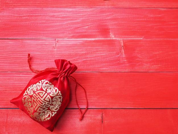 Китайский новый год фон. красный шелковистый мешок денег с строкой на естественной предпосылке древесины сосны и космосе экземпляра.