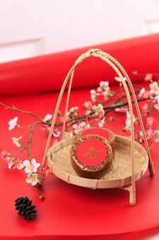 Китайский новогодний торт (kue keranjang - индонезия) с китайским иероглифом «фу» означает удачу. подается на бамбуковой тарелке, красное украшение имлек