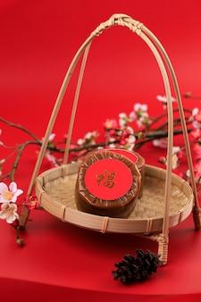 Китайский новогодний торт (китайский иероглиф «фу» означает удачу). популярный как куэ керанжанг или додол китай в индонезии. подается на бамбуковой тарелке, украшение из цветов имлек, место для текста