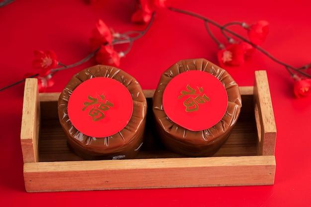 Китайский новогодний торт (китайский иероглиф «фу» означает удачу). популярный как куэ керанжанг или додол китай в индонезии. подается на бамбуковой тарелке, украшение из цветов имлек