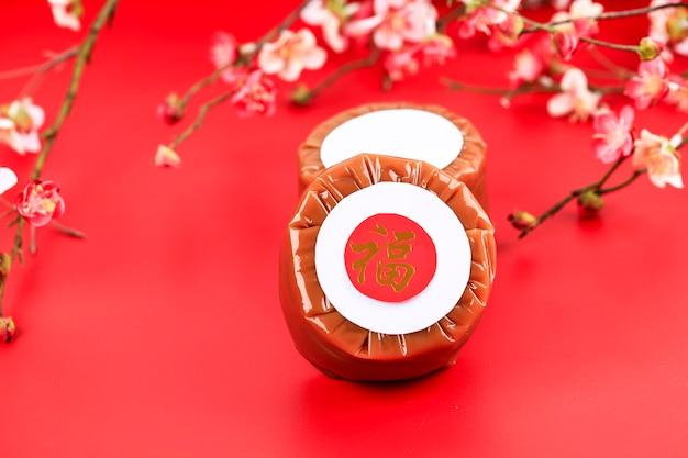 Китайский новогодний торт (китайский иероглиф «фу» означает удачу). популярный как куэ керанжанг или додол китай в индонезии. подается на бамбуковой тарелке, имлек красный фон