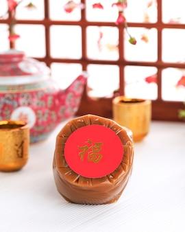 Китайский новогодний торт (китайский иероглиф «фу» означает удачу). популярный как куэ керанжанг или додол китай в индонезии. подается на бамбуковой тарелке, красное украшение имлек