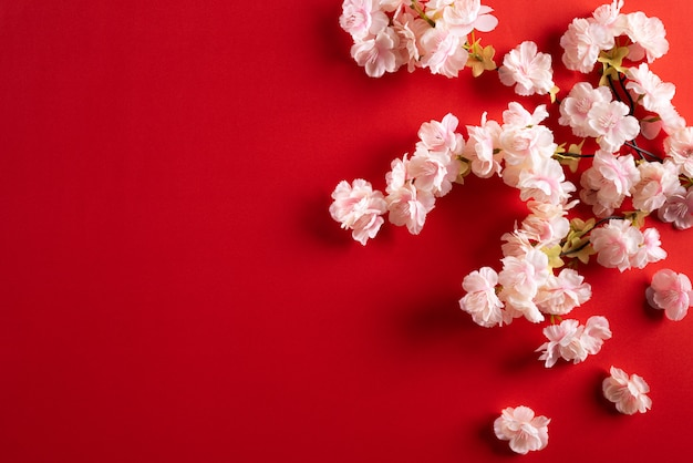 Chinese new year decorations, plum flowers blossom on red background