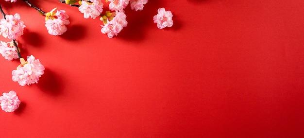 赤い背景に梅の花から作られた中国の旧正月のお祭りの装飾