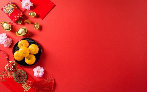 中国の旧正月の装飾の捕虜または赤いパケット、オレンジと金のインゴット