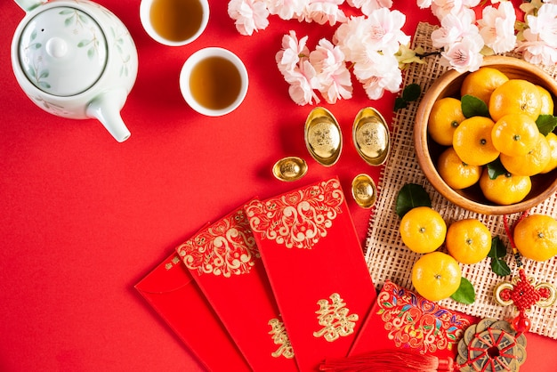 Chinese new year festival decorations pow or red packet, orange and gold ingots or golden lump on a red background. chinese characters fu in the article refer to fortune good luck, wealth, money flow.