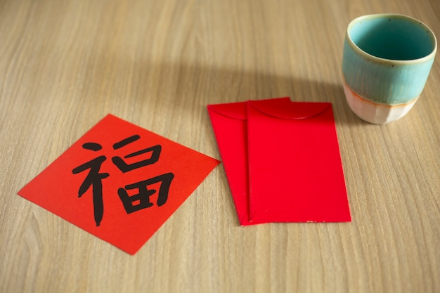 Chinese new year and lunar new year celebrations with giving red envelope and hot tea. the chinese word means : blessing, happiness and lucky
