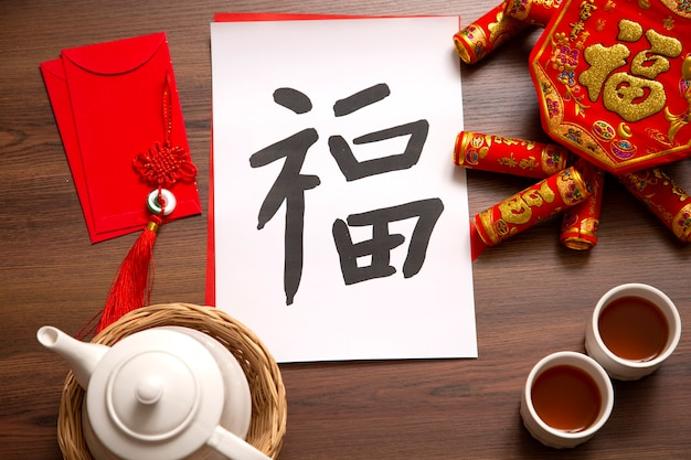 Chinese new year and lunar new year celebrations with gold bar giving red envelope and hot tea. the chinese word means : blessing, happiness and lucky