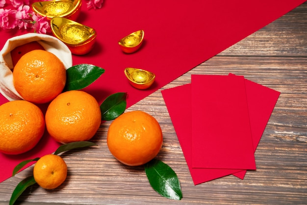 Chinese new year offering red envelope and orange, translation of text appear in image: prosperity, rich and healthy