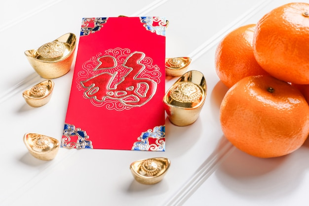 Chinese new year red ang pow with gold ingots and tangerine on table,chinese language mean