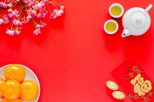 Китайский новый год красный фон с чайным сервизом, пакетами красных конвертов или анг бао (слово означает богатство), золотыми слитками, апельсинами и цветами китайского цветения.