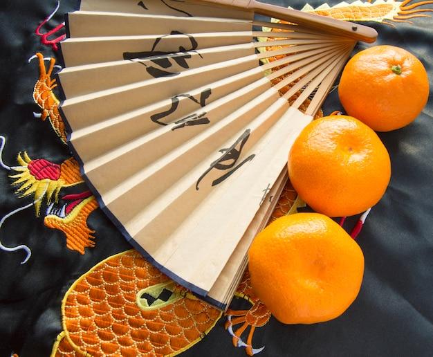 중국 새해, 귤과 자수 드래곤과 실크 직물에 누워 팬