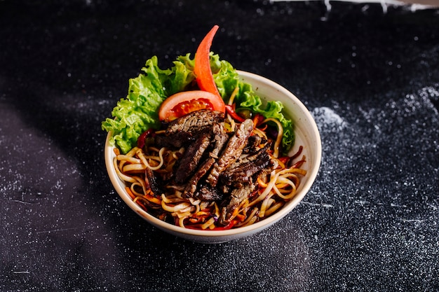 Chinese noodles inside bowl with chopped steak, tomato slices and lettuce.