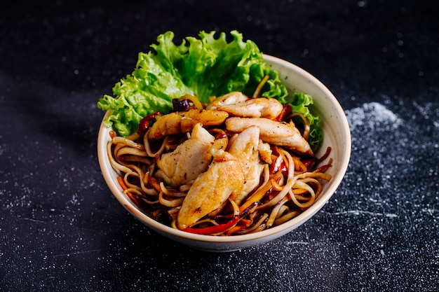 Chinese noodles inside bowl with fillet and lettuce.
