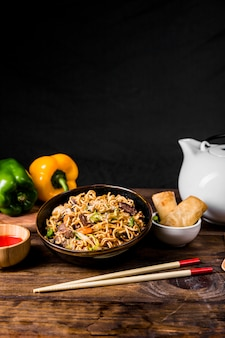 Chinese noodles with beef and vegetables served with spring rolls on wooden desk