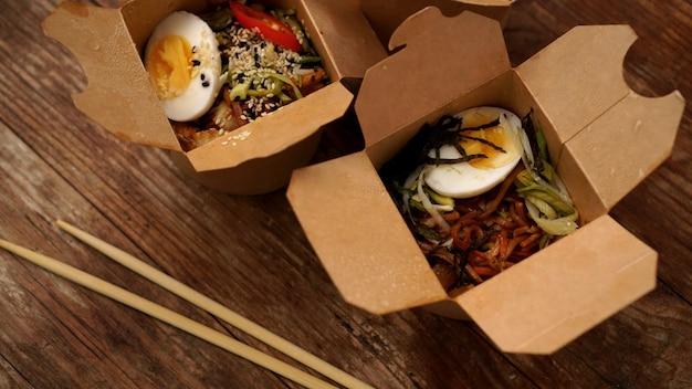 木製の背景の段ボール箱に鶏肉と野菜の中華麺、アジア料理の配達、屋台の食べ物の概念、コピースペース