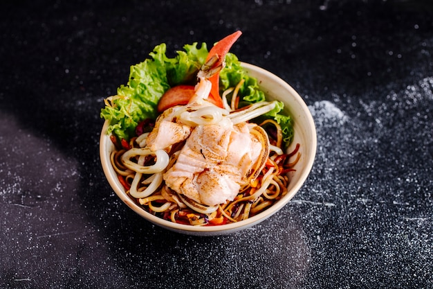 Chinese noodles with fish fillet, tomato and lettuce inside bowl.