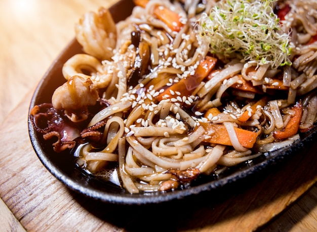Chinese noodles with mussels and shrimps on the wooden table.
