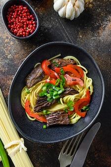 Китайская лапша с овощами и говядиной в черной миске