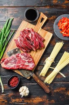 野菜入り中華麺、。木製の背景の上にマチェーテステーキと肉屋の包丁。上面図。