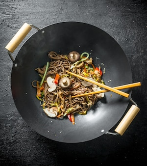 Chinese noodles wok soba in a frying pan with chopsticks on black wooden table