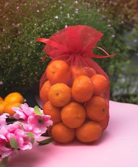 Китайский оранжевый мешок на розовой доске, свежие фрукты для счастья