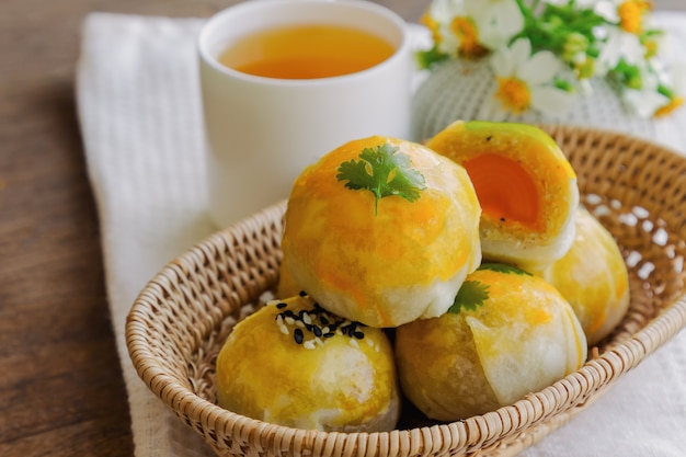 Chinese pastry or moon cake filled with mung bean paste and salted egg yolk served with tea