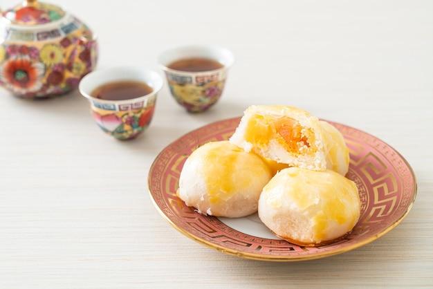 Лунный пирог из китайского теста с соленым яйцом и арахисом или спринг-ролл с орехами и солеными яйцами - азиатский стиль еды