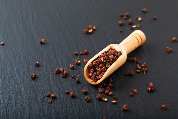 Chinese peppercorn, sichuan pepper in wooden scoop on black slate stone plate with copy space