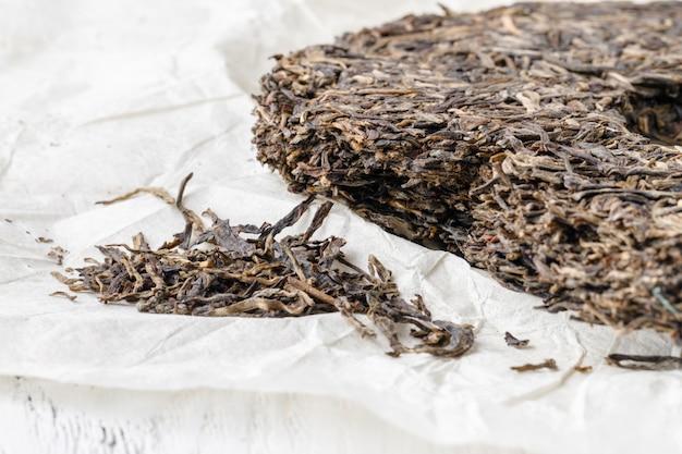 Китайский прессованный чай пуэр на упаковочной бумаге, крупный план