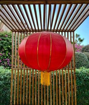 Китайская красная лампа или фонарь висит на деревянной террасе ресторана или кафе. новогоднее украшение в китае. фон празднования фестиваля фонарей